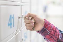 Die nahe hohe Hand, die den Schlüssel hält, öffnet den Bankkasten sicheres d lizenzfreies stockbild