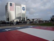 Die NASA-Fahrzeugmontage-Gebäude und US-Flagge stockbild