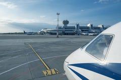Die Nase eines Flugzeuges mit dem Minsk-Flughafen im Abstand Lizenzfreie Stockfotos