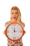 Die nette blonde Frau mit einer großen orange Uhr gestikulierend seiend spät ist Lizenzfreie Stockfotos