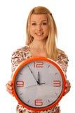 Die nette blonde Frau mit einer großen orange Uhr gestikulierend seiend spät ist Stockfoto