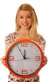 Die nette blonde Frau mit einer großen orange Uhr gestikulierend seiend spät ist Lizenzfreies Stockbild