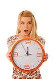 Die nette blonde Frau mit einer großen orange Uhr gestikulierend seiend spät ist Stockbilder