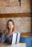Die nette blonde weibliche Person, die Gesichter mit den Zeigefingern macht, nähern sich Laptop Lizenzfreie Stockbilder
