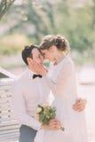 Die nette junge blonde Braut, die auf den Knien des Bräutigams parken sitzt im Frühjahr Stockbild