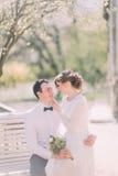 Die nette junge blonde Braut, die auf den Knien des Bräutigams parken sitzt im Frühjahr Stockfotografie