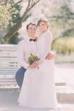 Die nette junge blonde Braut, die auf den Knien des Bräutigams parken sitzt im Frühjahr Stockbilder