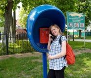 Die nette schwangere Frau nennt vom Münztelefon Am stan Lizenzfreies Stockfoto