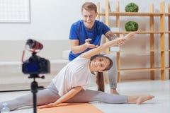 Die netten Bloggers, die Sport tun, trainiert vor der Kamera Lizenzfreie Stockfotos