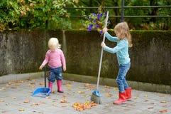 Die netten kleinen ausgedehnten Mädchen trocknen Blätter auf Herbst Stockfotografie