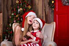 Die netten Mädchen, die mit Geschenken sitzen, nähern sich Weihnachtsbaum in Sankt-Kostümen, lächeln und haben Spaß Weihnachtsatm Stockfotos