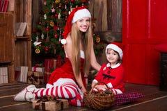 Die netten Mädchen, die mit Geschenken sitzen, nähern sich Weihnachtsbaum in Sankt-Kostümen, lächeln und haben Spaß Weihnachtsatm Stockfoto