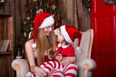 Die netten Mädchen, die mit Geschenken sitzen, nähern sich Weihnachtsbaum in Sankt-Kostümen, lächeln und haben Spaß Weihnachtsatm Lizenzfreie Stockbilder