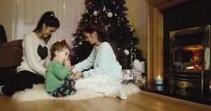 Die netten Schwestern, die Weihnachtsgeschenk für Eltern einwickeln, nähern sich Weihnachtsbaum Netter Sohn, der Apfel isst und w stock video footage