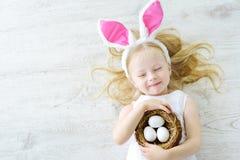 Die netten tragenden Häschenohren des kleinen Mädchens, die Ei spielen, jagen auf Ostern Lizenzfreies Stockfoto