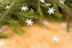 Die Niederlassungen von Weihnachtsbäumen auf dem Hintergrund von hölzernen Brettern und von Schneeflocken Lizenzfreie Stockfotografie