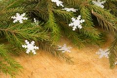 Die Niederlassungen von Weihnachtsbäumen auf dem Hintergrund von hölzernen Brettern und von Schneeflocken Stockfoto