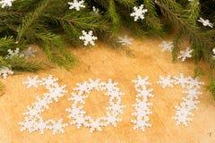 Die Niederlassungen von Weihnachtsbäumen auf dem Hintergrund von hölzernen Brettern und von Schneeflockenaufschrift Stockfoto