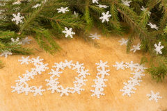Die Niederlassungen von Weihnachtsbäumen auf dem Hintergrund von hölzernen Brettern und von Schneeflockenaufschrift Stockfotografie