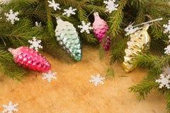 Die Niederlassungen von Weihnachtsbäumen und von fallal Kegeldekorationen auf dem Hintergrund von hölzernen Brettern und von Schn Stockfoto