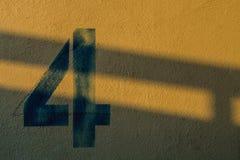 Die Nr. 4 auf der Wand im Schatten der Lichter Lizenzfreies Stockbild