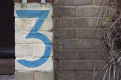 Die Nr. drei gemalt auf einer Backsteinmauer Stockbild