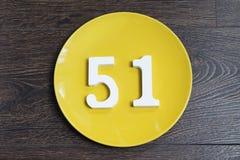 Die Nr. einundfünfzig auf der gelben Platte Stockfotos