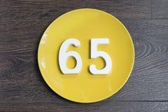 Die Nr. fünfundsechzig auf der gelben Platte Stockfoto