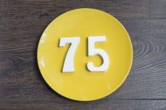 Die Nr. fünfundsiebzig auf der gelben Platte Stockfoto