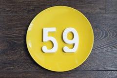 Die Nr. neunundfünfzig auf der gelben Platte Stockbilder