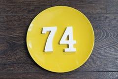 Die Nr. vierundsiebzig auf der gelben Platte Stockfotografie