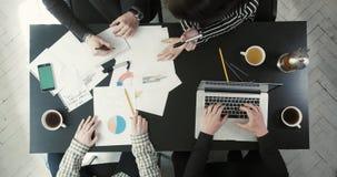 Die oben genannte Ansicht der Hände von vier Leuten, die Geschäftszeitpläne und -graphiken, schreibend auf dem Laptop und dem Tri stock footage