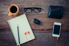 Die Oberfläche eines Holztischs mit einem Notizbuch, Smarttelefon, Gläser, Geldbörse, Autoschlüssel, Kaffeetasse lizenzfreies stockfoto