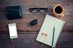 Die Oberfläche eines Holztischs mit einem Notizbuch, Smarttelefon, Gläser, Geldbörse, Autoschlüssel, Kaffeetasse stockfotografie