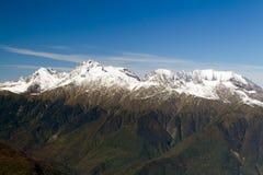 Die Oberteile der Berge bedeckt mit Schnee Die Steigungen sind thic Stockfoto