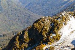 Die Oberteile der Berge bedeckt mit Schnee Die Steigungen sind thic Lizenzfreie Stockfotos