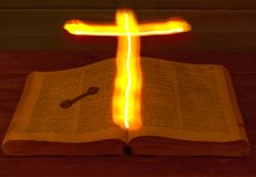 Die offene heilige Bibel ist auf dem Tisch Alte Taste Das heilige Kreuz glüht über die Bibel und belichtet seine Seiten Brennende Lizenzfreie Stockbilder