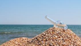 Die offene leere Flasche lag auf einem Hügel des Sandes Stockbilder