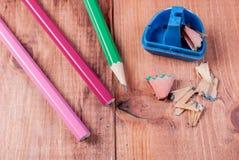 Die offenen zensieren den Bleistiftspitzer und Bleistifte, die auf einem hölzernen Hintergrund liegen Stockbild