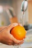 Die Orange wird im Wasser gewaschen Lizenzfreies Stockbild