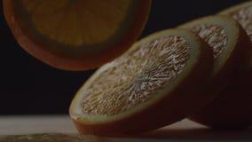 Die Orange wird in Kreise geschnitten, liegen orange Kreise nacheinander, hält die Hand ein Stück der Orange und entfernt es ist stock video footage