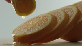Die Orange wird in Kreise, orange Kreise liegen nacheinander, die Hand hält ein Stück der Orange über der anderen geschnitten stock video footage