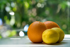 Die organische Orange und die Zitrone auf Grün verwischten backgroun Stockbild