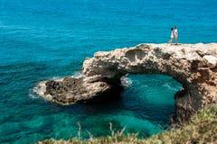 Die Paare auf der Klippe durch das Meer Stockbilder