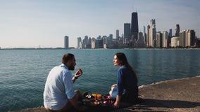 Die Paare, die auf Ufer von Michigan See sitzen und Frühstücksmann und -frau essen, haben Picknick nahe Wasser in Chicago stock footage