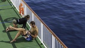 Die Paare, die auf Fähre bei der Aufwartung zum Segel stillstehen Stockfotos