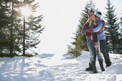 Die Paare, die auf Schnee stehen, bedeckten Hügel stockfotos