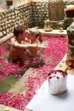 Die Paare, die im Blumen-Blumenblatt sich entspannen, bedeckten Pool Stockbild