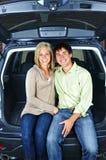 Die Paare, die innen sitzen, ziehen sich vom Auto zurück Stockbilder
