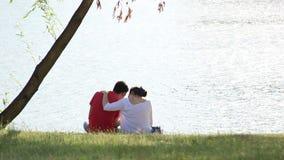 Die Paare, die zusammen auf dem Strand nahe den Palmen sitzen, sprechen, beruhigen stock video footage
